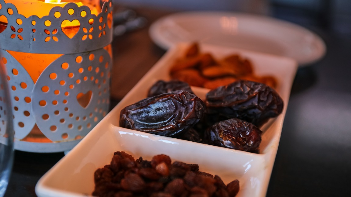 A candle and a partitioned little tray featuring dates for iftar.