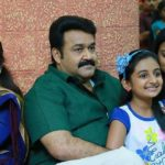 """Image from """"Drishyam"""": A family sits together at a shopping mall. Via letterboxd.com"""