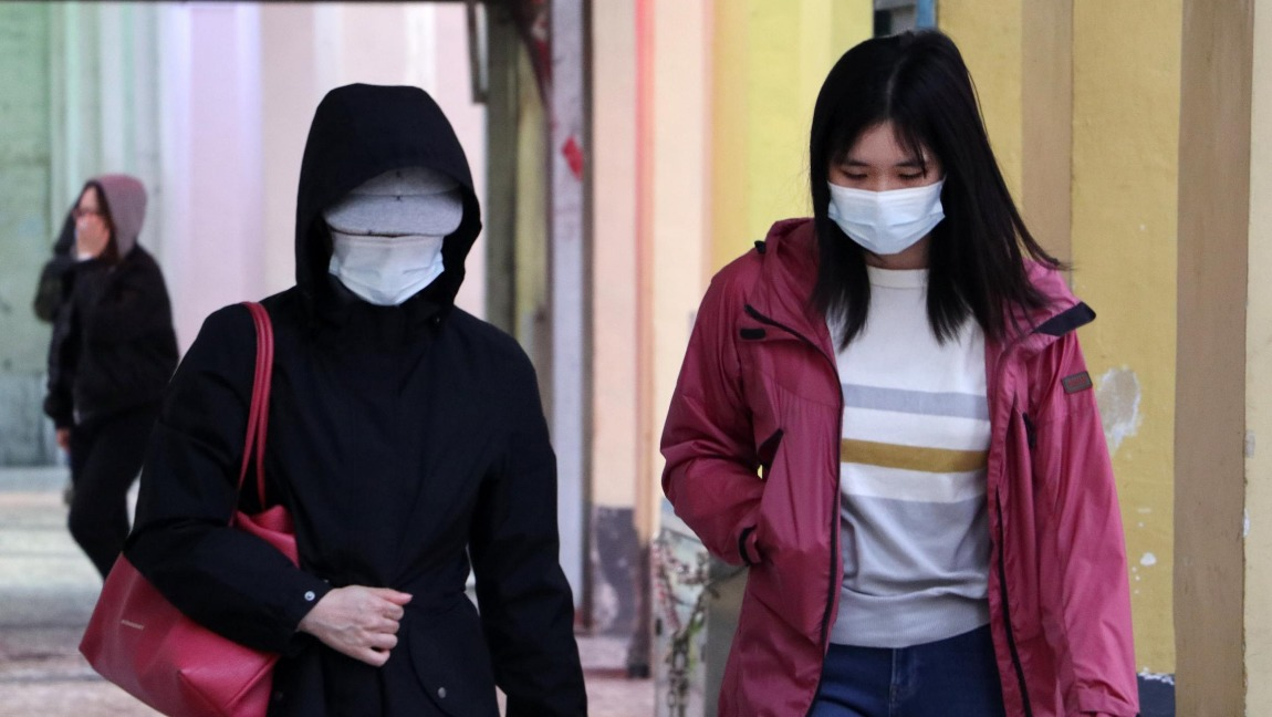 Two people wearing masks walk side by side.