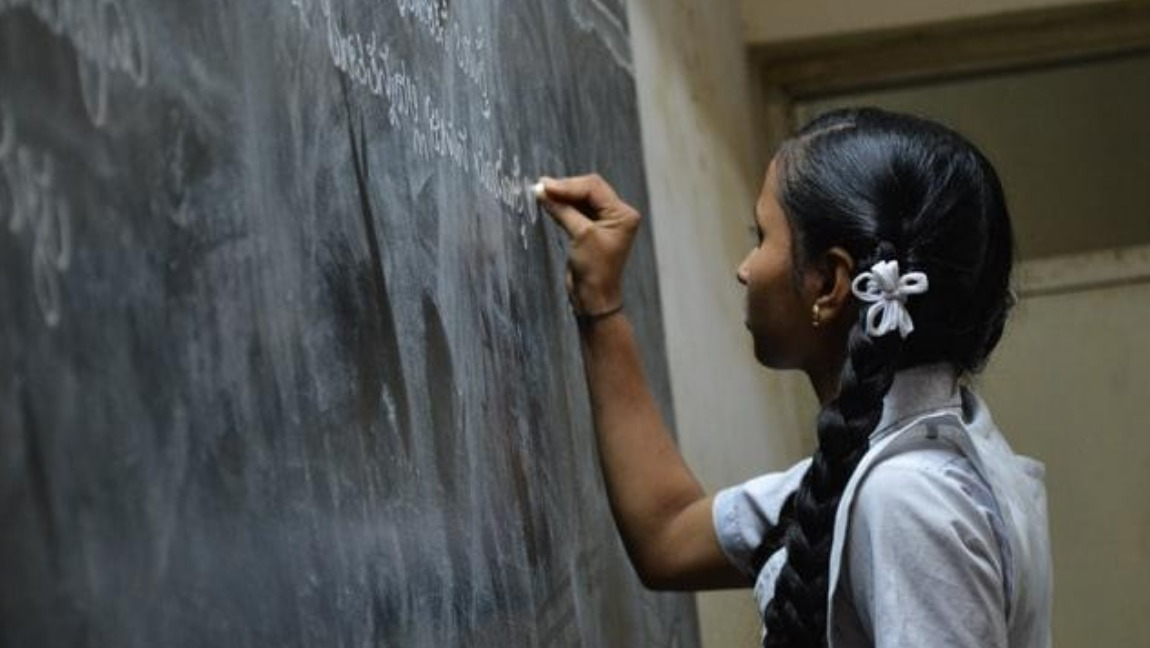 [Image Description: An Indian school girl is writing on a blackboard] Via Unsplash