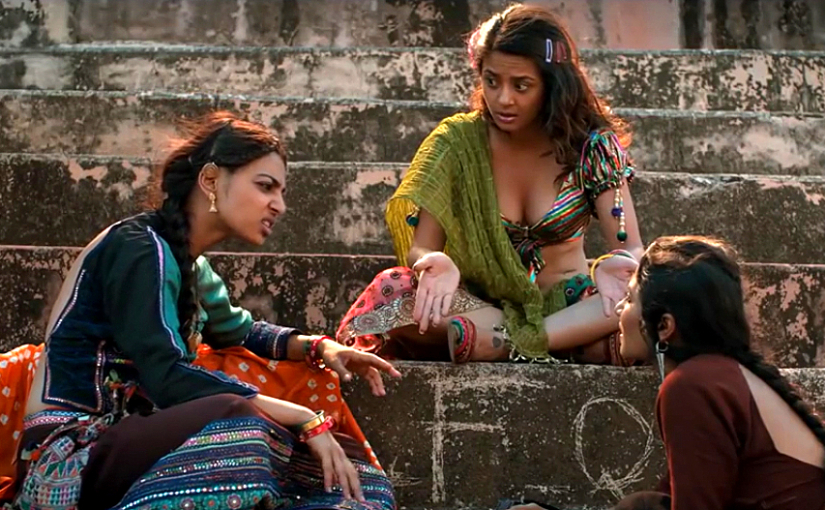 The image shows three Indian rural women sitting on the stairs and talking to each other.
