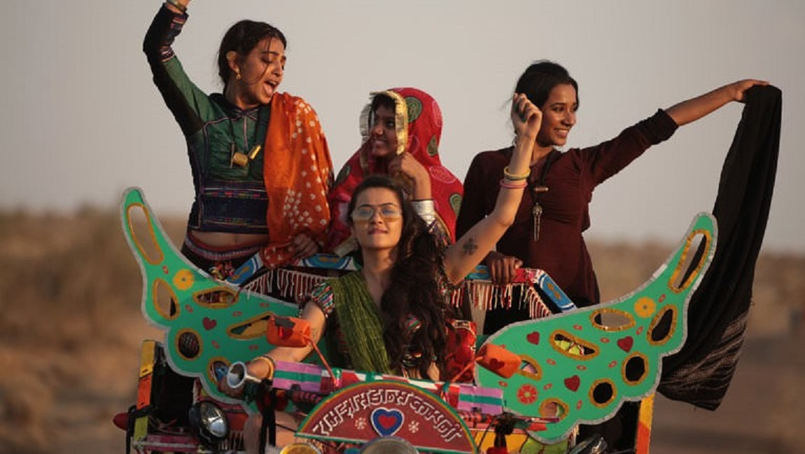 The image shows four women dressed in rural Indian village attire having fun on a vehicle.