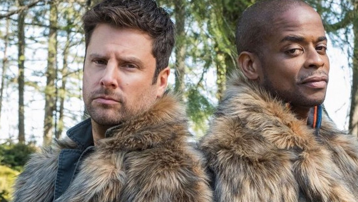 Two men wearing fur coats stand back to back in the woods. Via denofgeek.com.