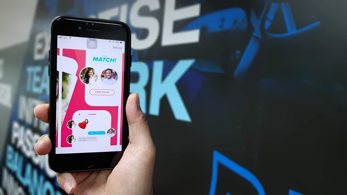 a person holds up their iPhone showing the popular online dating app Tinder.