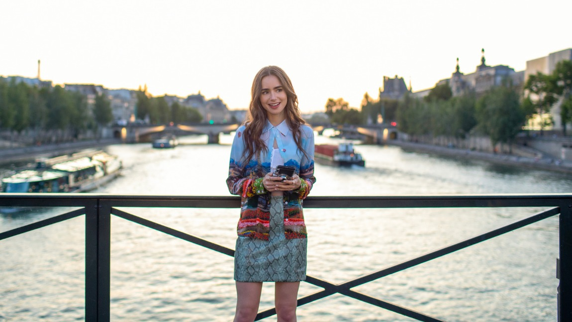 "[Image description: Still from ""Emily In Paris"" - a brunette girl (Lily Collins) stands on a bridge holding her phone in both hands.] Via Netflix"