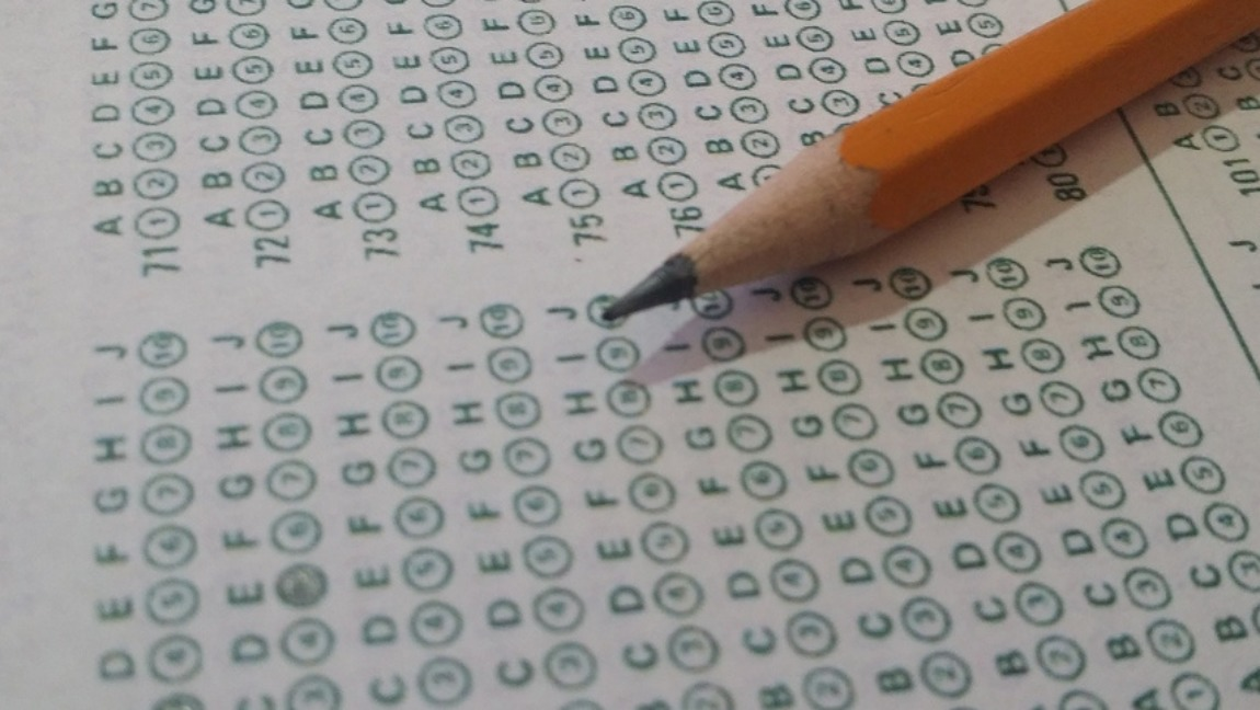 [Image description: Pencil on top of SAT test papers.] via Shutterstock