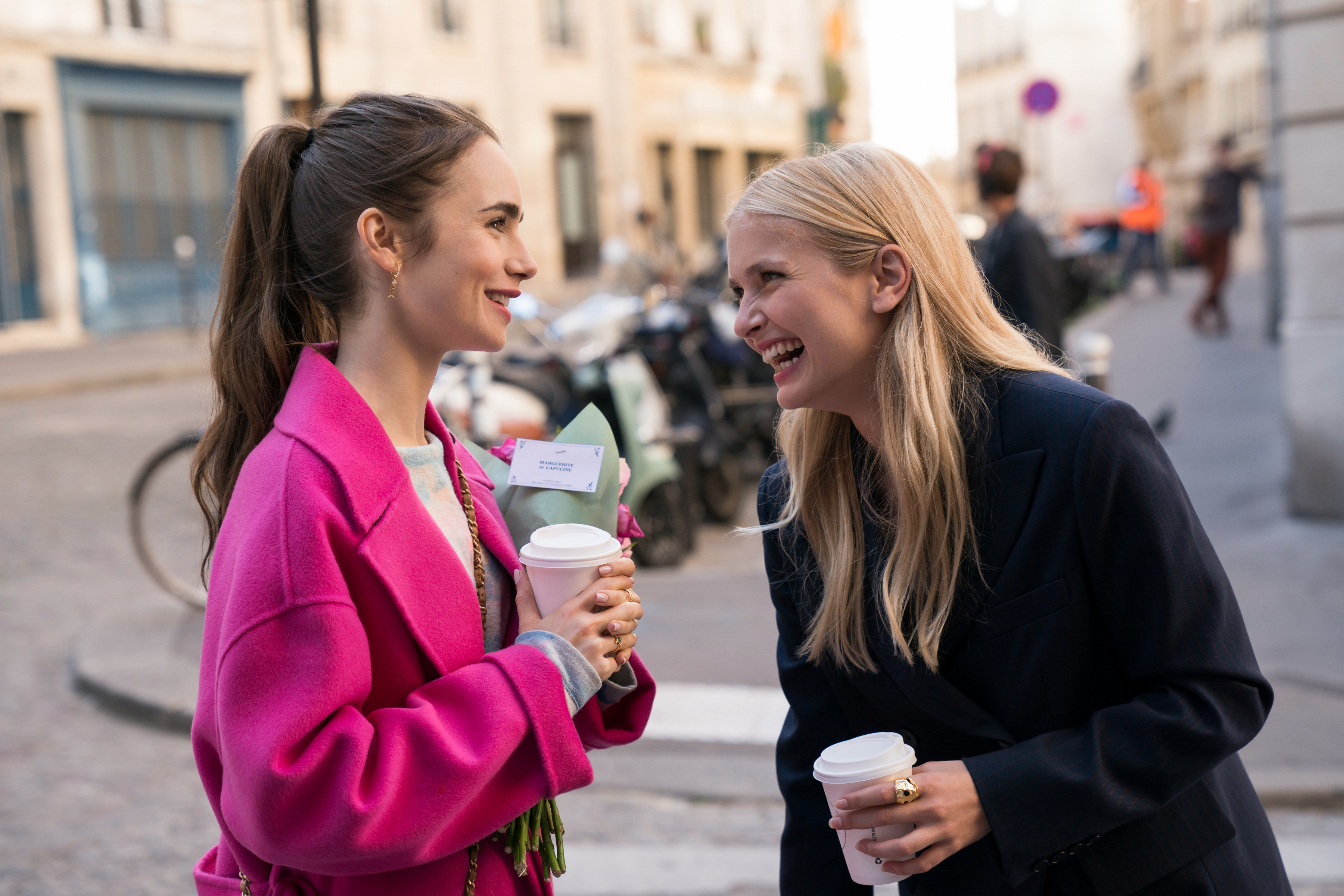 "[Image description: still from ""Emily In Paris"" - a brunette girl, Emily, and a blond girl, Camille, stand close and laugh at a joke Emily has made.] Via Netflix"