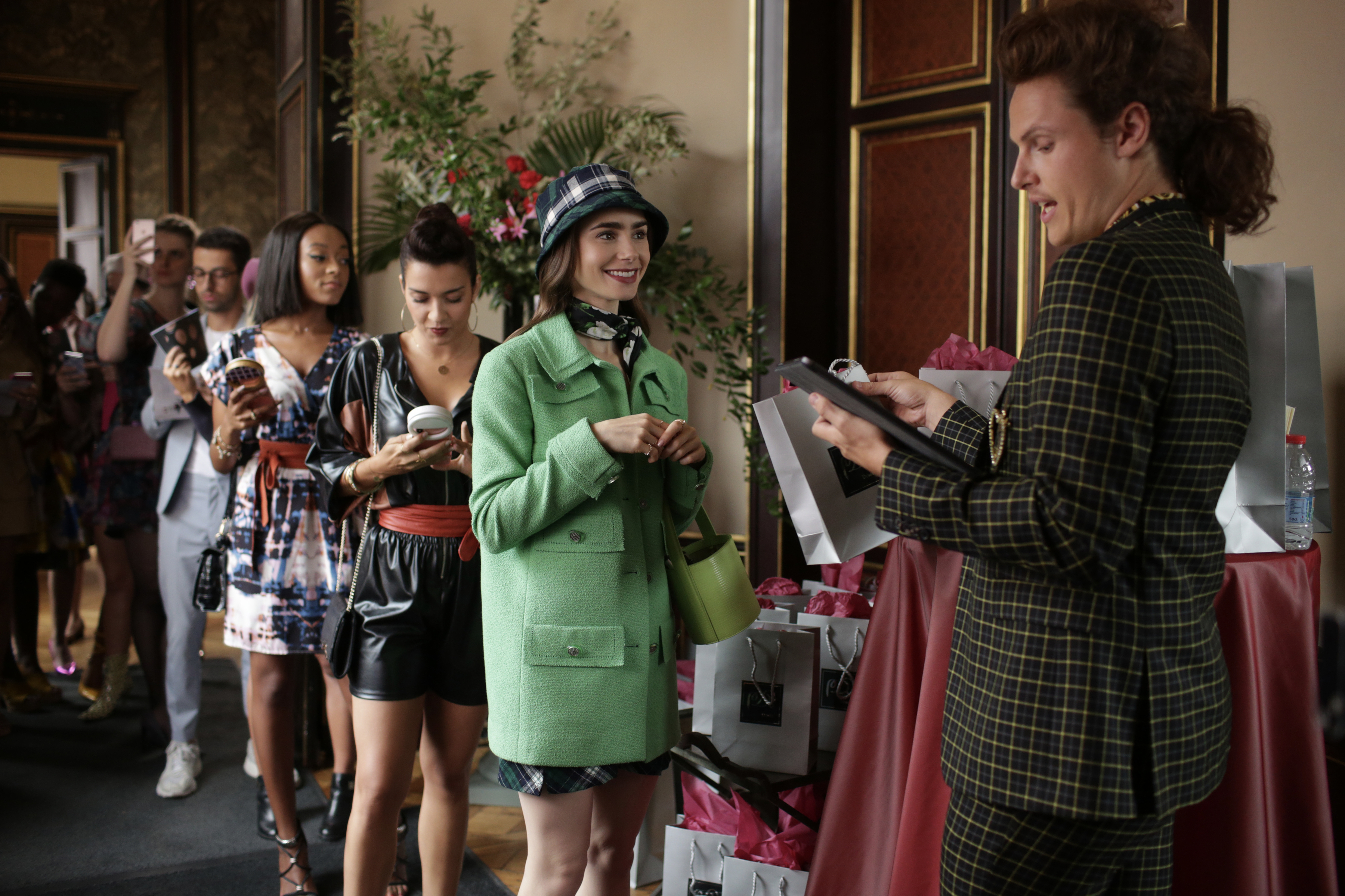[Image description: Emily, wearing a green coat and a hat, stands in line ahead of other girls who are all dressed fashionably and holding their phones] Via Netflix