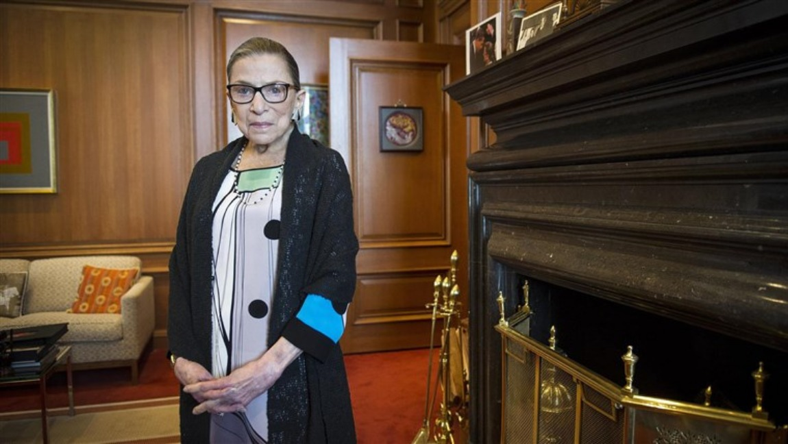 [Image description: RBG stands and faces the camera, standing in a stately position.] via NBC News