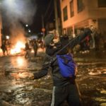 [Image description: Young man uses a slingshot to throw stones at police during protests] Via AP Photo/Ivan Valencia