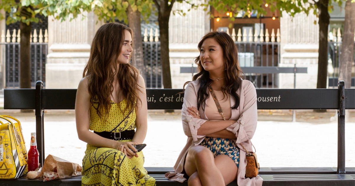 "[Image description: still from ""Emily In Paris"" - two women, a brunette wearing yellow (Lily Collins) and a black-haired one with her arms crossed wearing pink (Ashley Park) sit on a bench together, grinning at each other] Via Netflix"