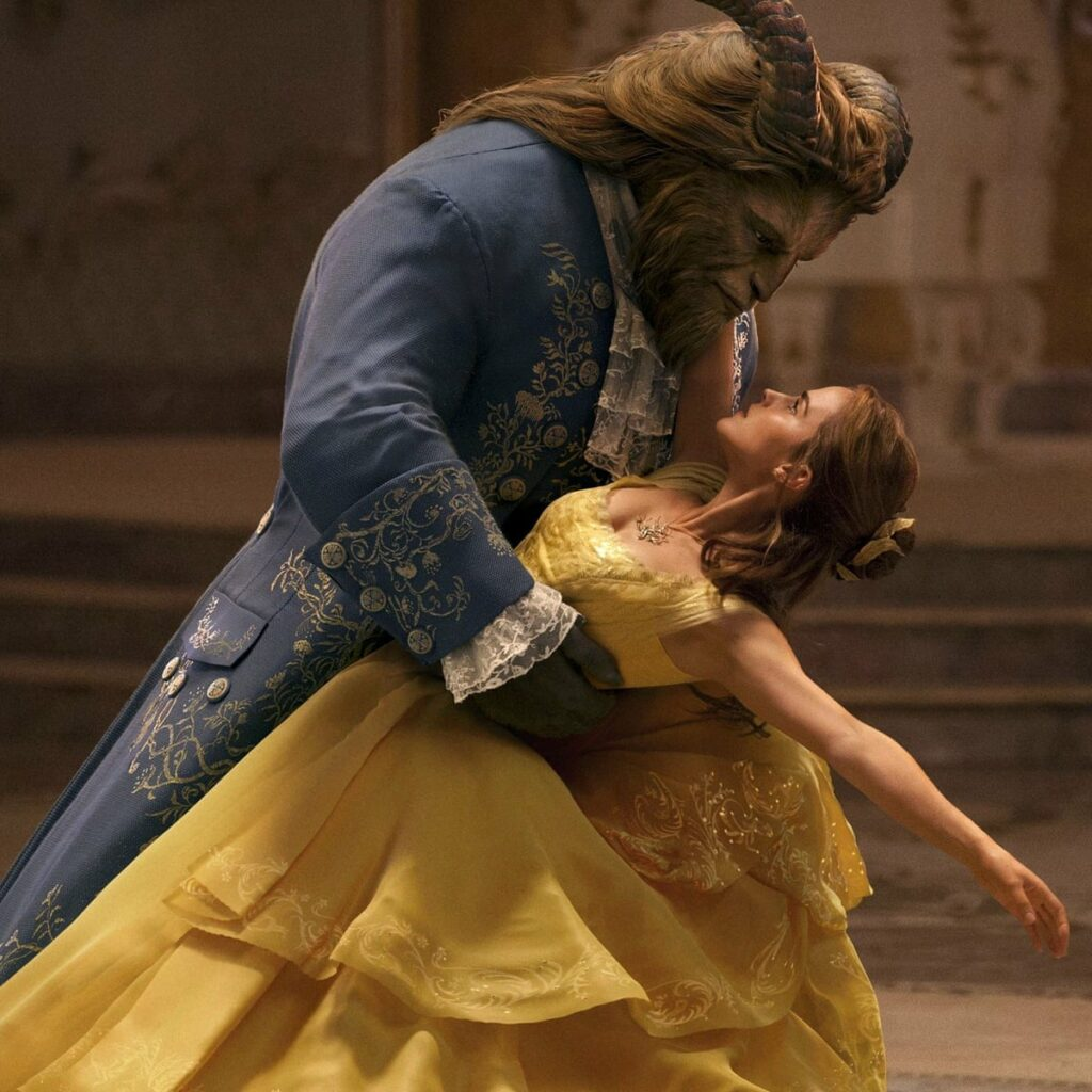 [Image Description: dancing scene from the live-action Beauty and the Beast, with Belle in a yellow dress dancing with the Beast] via Disney.