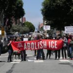 "A group of people standing in the middle of the street holding a red banner that reads, ""Abolish Ice."""