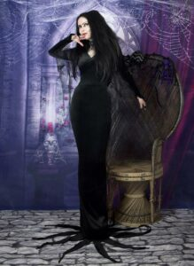 Woman wearing long, black Mortitia Addams themed dress and posing with her hand under chin