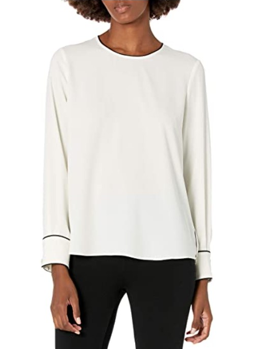 [Image description: A woman wearing a white long-sleeve blouse.] via Amazon