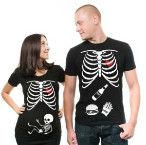 [Image Description: A man and a woman wear black shirts with skeleton prints on them. The woman's shirt has a baby skeleton in the stomach area and the man's has a beer, a burger and fries.]