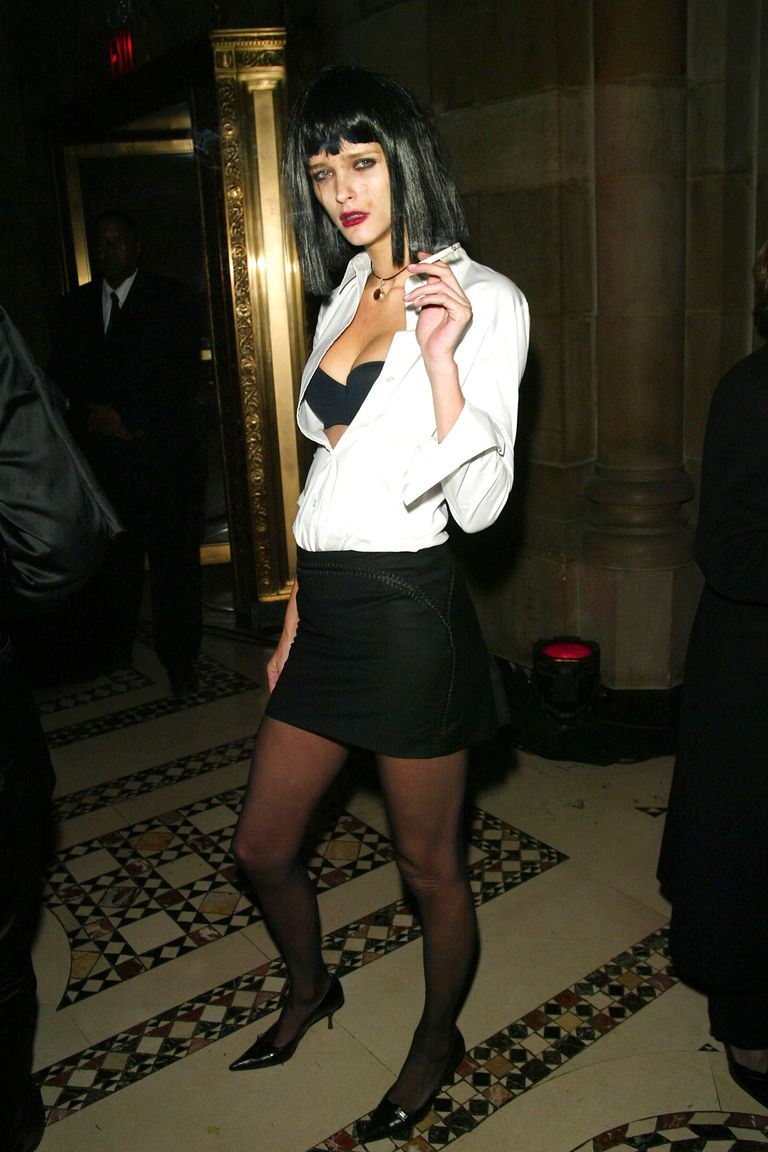 Carmen Kass as Mia Wallace fromPulp Fiction, wearing the iconic blunt cut black wig, open white button-down shirt with the black bra showing, the black mini with black tights pantyhose and heels. She had a cigarette in her hand and the signature nose bleed as in the movie.