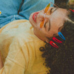 [Image description: Woman laying down on the grass wearing a yellow shirt, jeans, and orange sunglasses.] via Pexels.