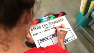 Director Debbie Rao writes the name of the show on the slate