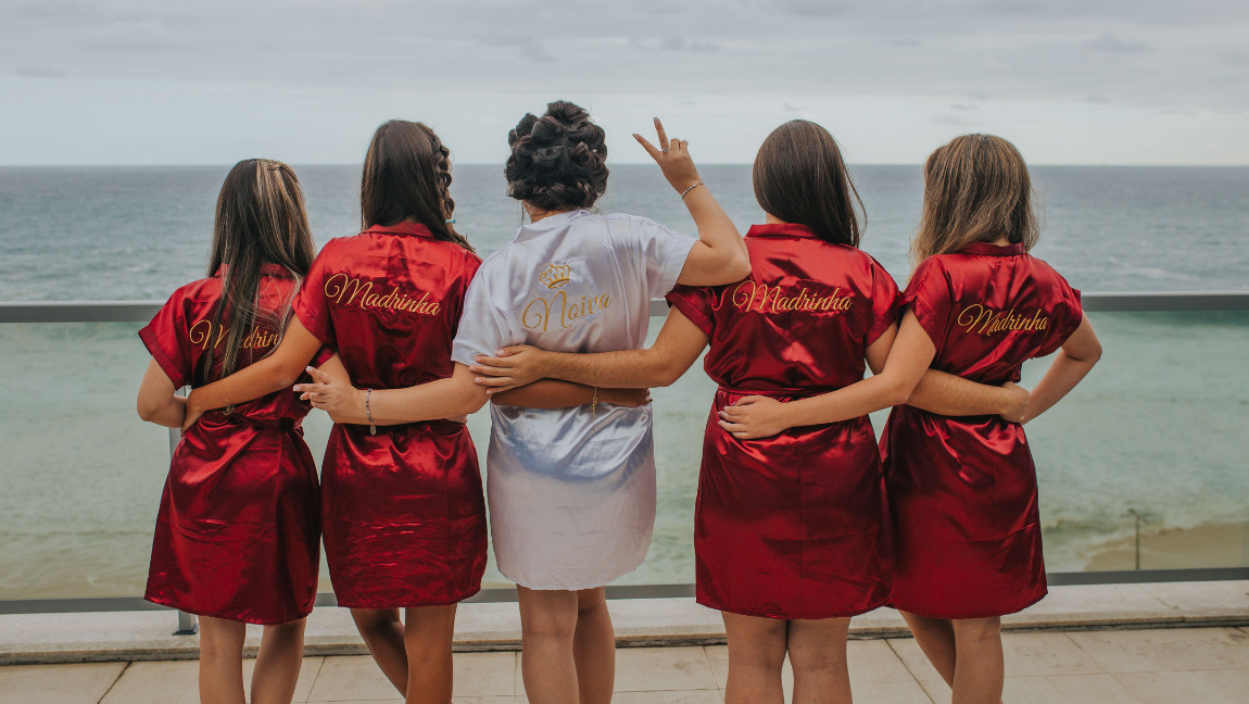 [Image description: five women in knee-length silk gowns looking towards the ocean. The women in the center is wearing while silk gown and holding up the peace sign. The other four women are wearing red silk gowns.] via Unsplash