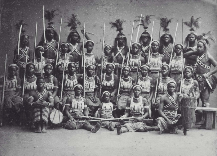 A group of women and men, the N'Nonmiton/Dahomey Amazons, in their ceremonial clothing, holding weapons