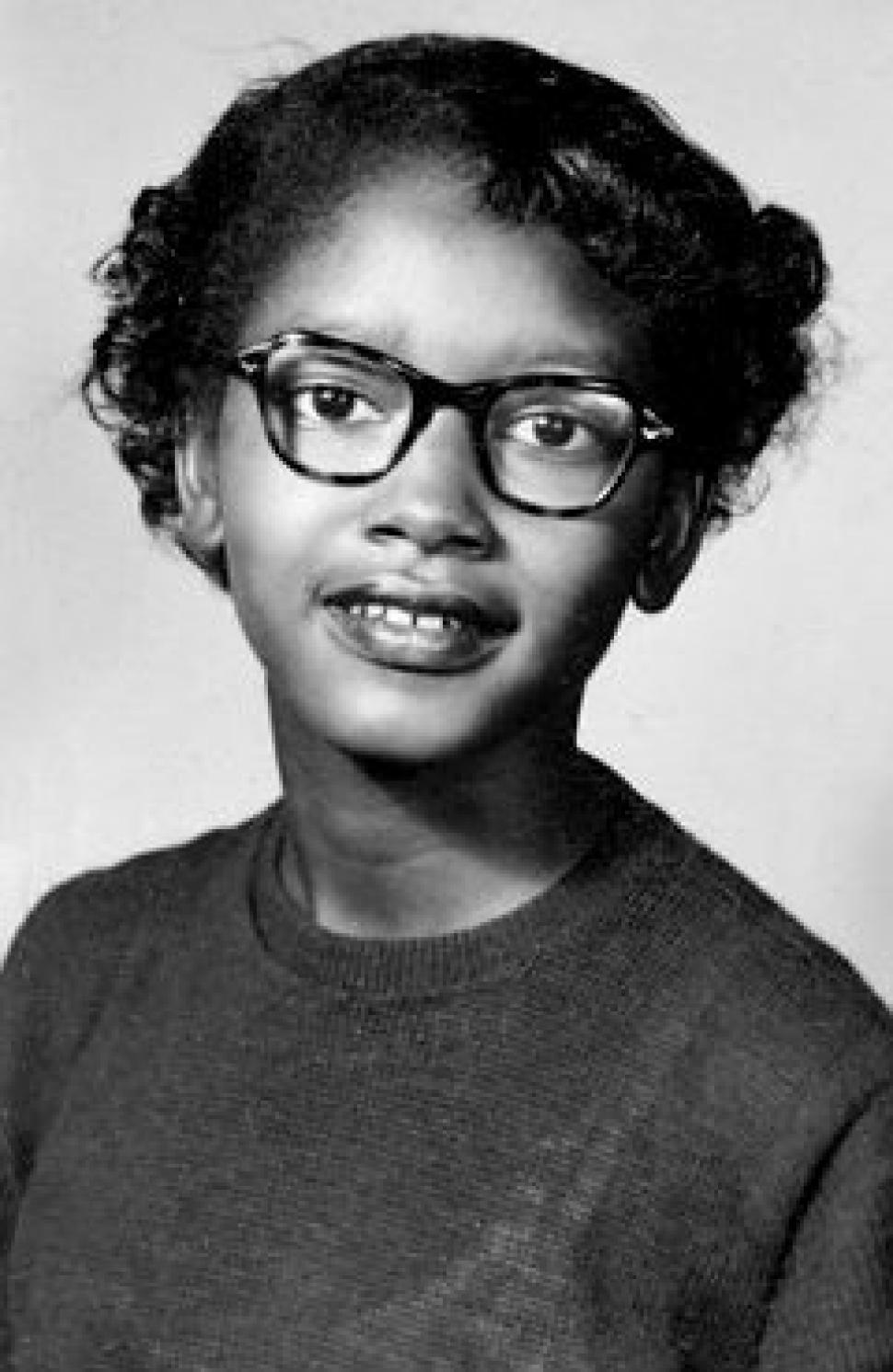 A black and white head shot of Claudette Colvin. She is wearing a plain shirt, glasses, and has short curly hair.