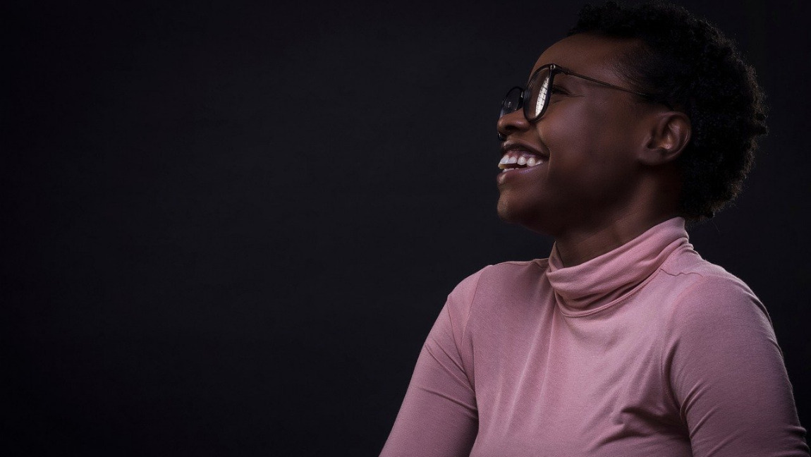 [Image description: A picture of a woman smiling while wearing a pink turtleneck and glasses.] Via Free Photos on Pexels