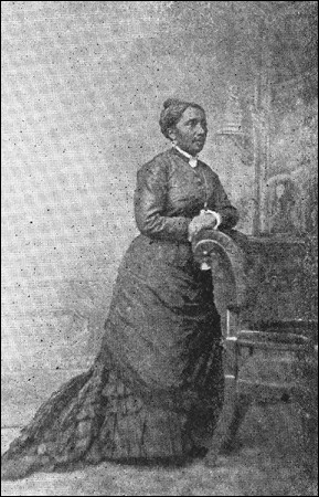 A black and white photo of Elizabeth Jennings posing in a long dress and standing with her arm resting on a chair.