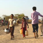 Three children walk in an arid landscape with vessels and a bicycle.