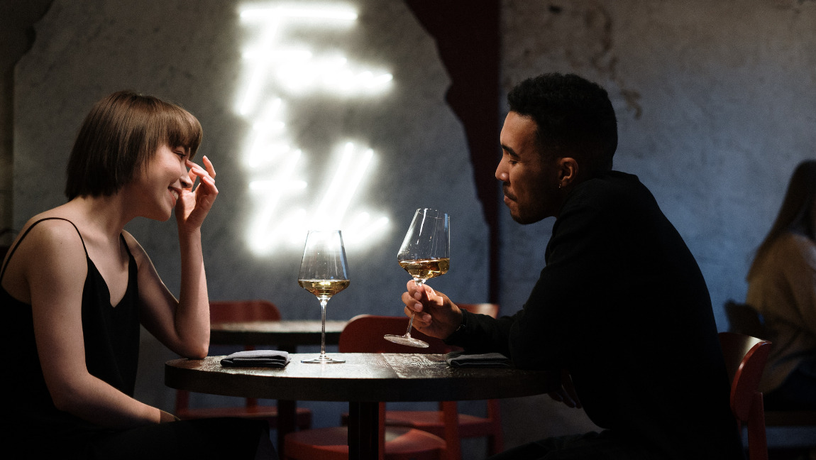 [Image description: a woman and a man seated at a restaurant table, the man is drinking a glass of wine.] via Pexels