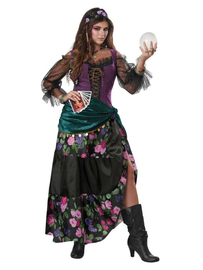 A woman holding tarot cards and a glass globe in a stereotypical costume.