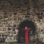 [Image description: a figure clad in red robes and Halloween mask hides in the dark arches of a church] Via Dan Burton on Unsplash