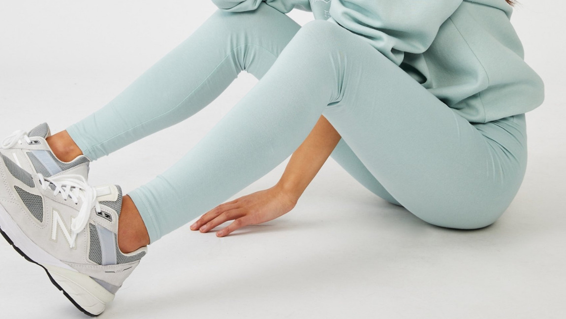 [Image Description: person sitting on the floor wearing sneakers, a pastel blue hoodie and leggings.] via Cotton On