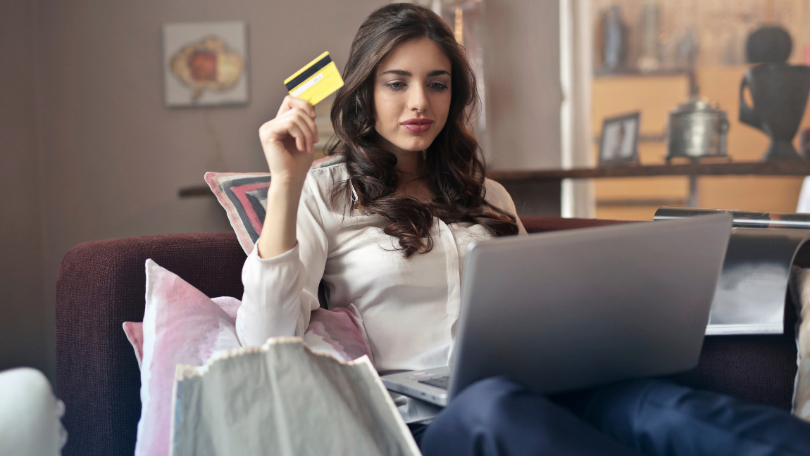 Woman using her laptop while holding a credit card.