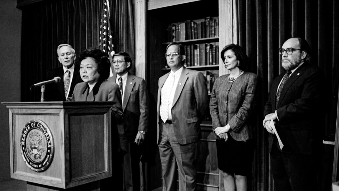 Patsy Mink stands at a podium to announce the creation of the Congressional Asian American Pacific Congress. Behind her, from left to right, stands Representatives Don Edwards and Norman Mineta, House Delegate Robert Underwood, Representatives Nancy Pelosi and Neil Abercrombie.