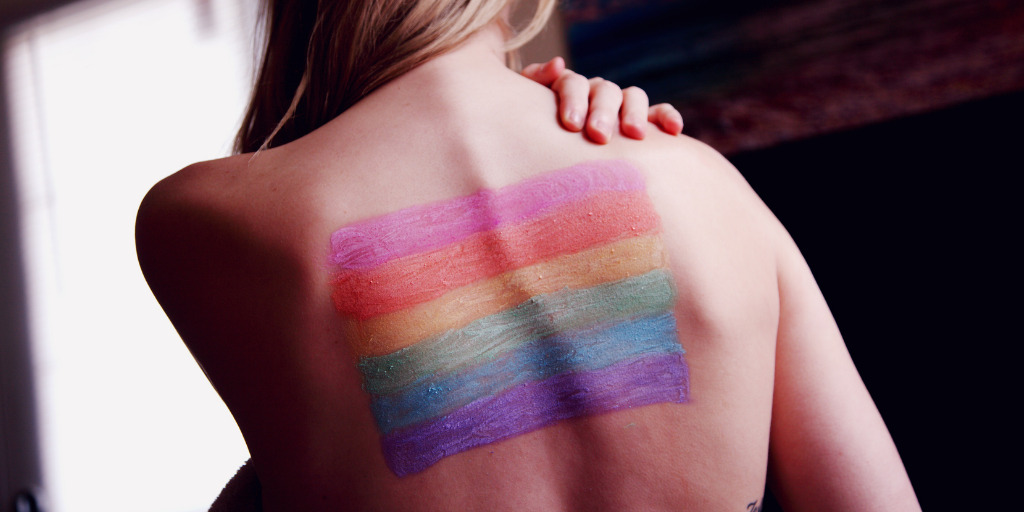 [Image description: A woman's back with the pride flag painted over it. ] Via Sharon McCutcheon on Pexels