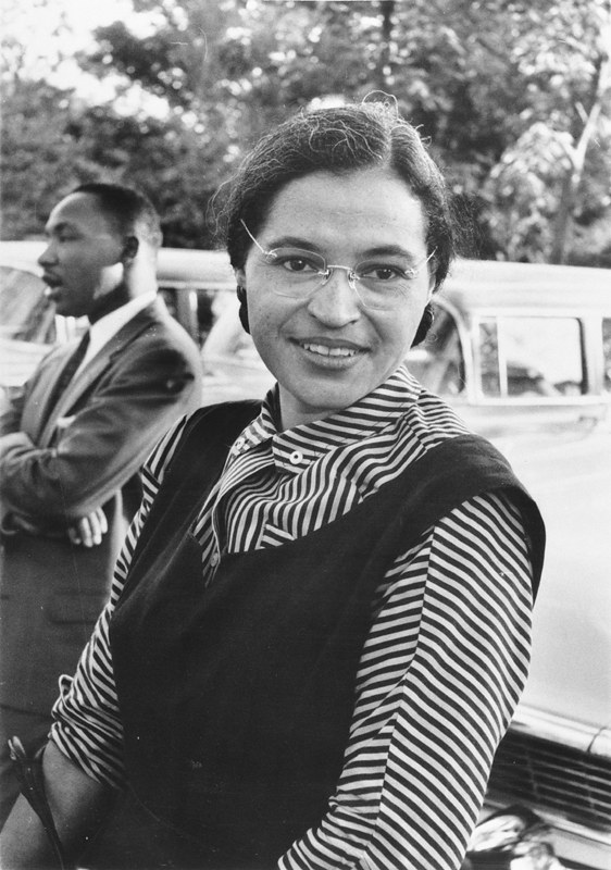 A picture of Rosa Parks smiling while sitting on a bench with Martin Luther King Jr. sitting in the background behind her.