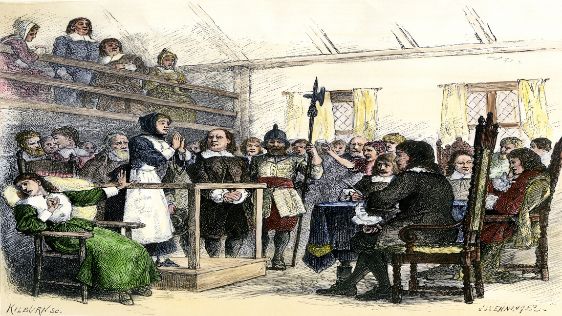 This is a drawing of a court scene from the Salem Witch Trials. A woman wearing a black and white dress is standing on a stand in the middle of the court in handcuffs and is surrounded by spectators.