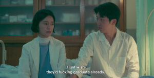 "Still from The School Nurse Files. A black-haired woman in a nurse's uniform, Ahn Eun-young sits next to a black-haired man, Hong In-pyo in the nurse's office. She is facing Hong In-pyo without looking at him, and has a tired expression. She tells him, ""I just wish they'd fucking graduate already."