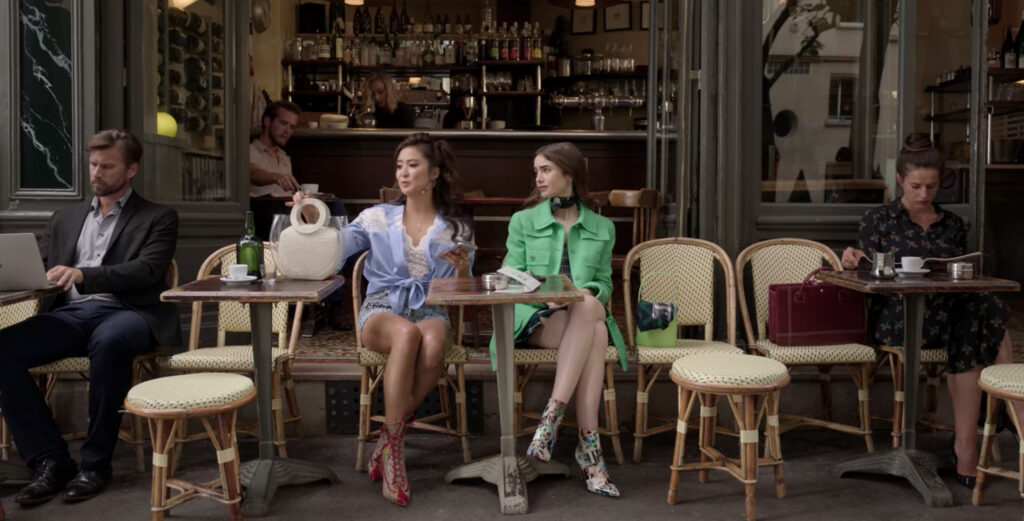 Mindy (left) and Emily (right) sit at a cafe. Mindy is wearing a blue shirt tied around the waist over a white top and shorts. Emily is wearing a green coat.