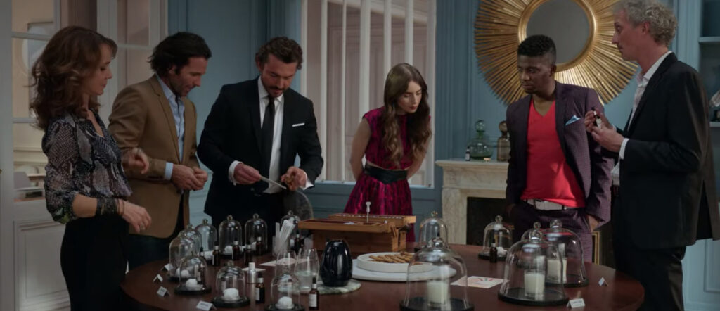 Emily, Sylvie, and male coworkers review Antoine's scents for a client. Emily is wearing a pink dress, Sylvie is wearing a black patterned top and black skirt, male coworkers are wearing shirts and blazers.