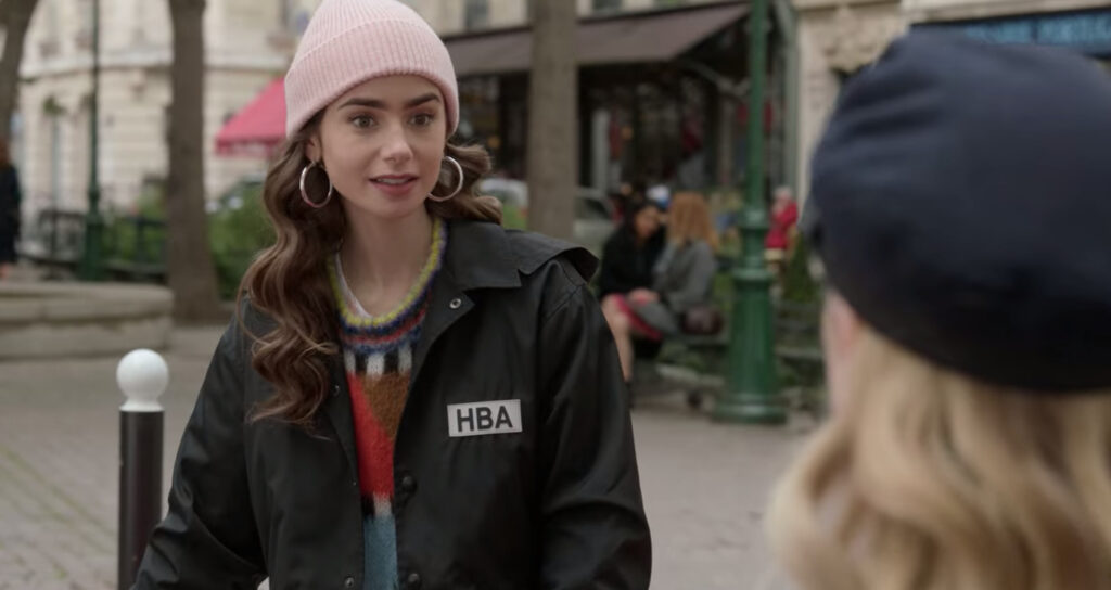 Emily is standing and talking to Camille with a worried expression on her face. Emily is wearing a pink beanie, hoop earrings, multi-colored sweater, and black jacket.
