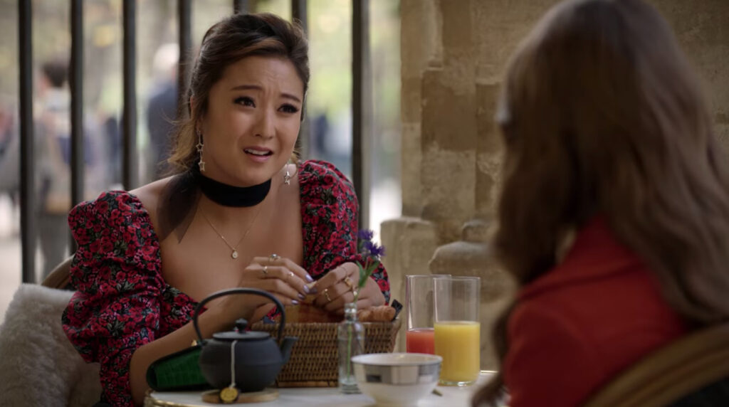 Mindy sits at a table with Emily. Mindy is wearing long earrings, a black choker, drop necklace, and a pink floral dress.