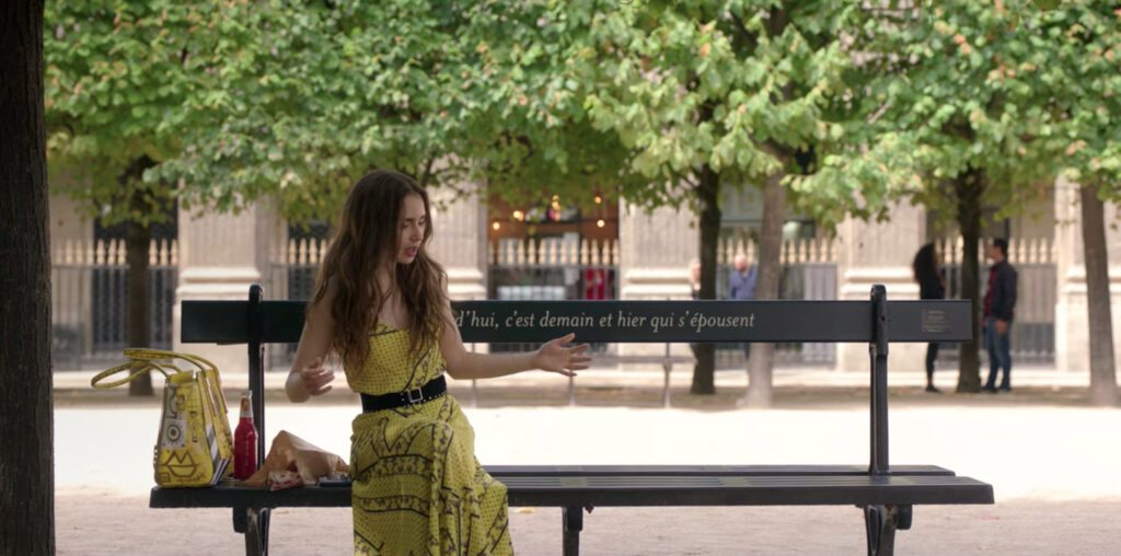 Emily sits on a park bench with her hands out and a frustrated expression on her face. Emily is wearing a long, yellow dress that features a pattern in black and a black belt around the waist.