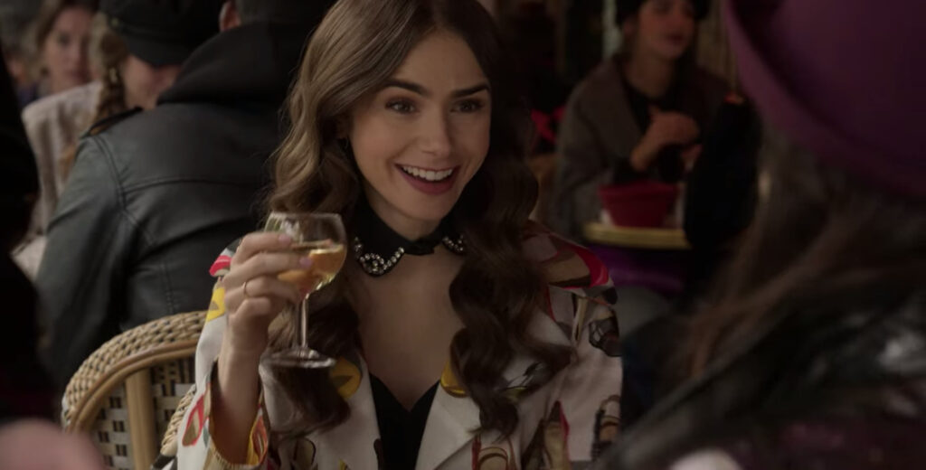 Emily sits with a glass of wine at a table. Emily is wearing a black, jeweled collar and jacket that features images of shoes.