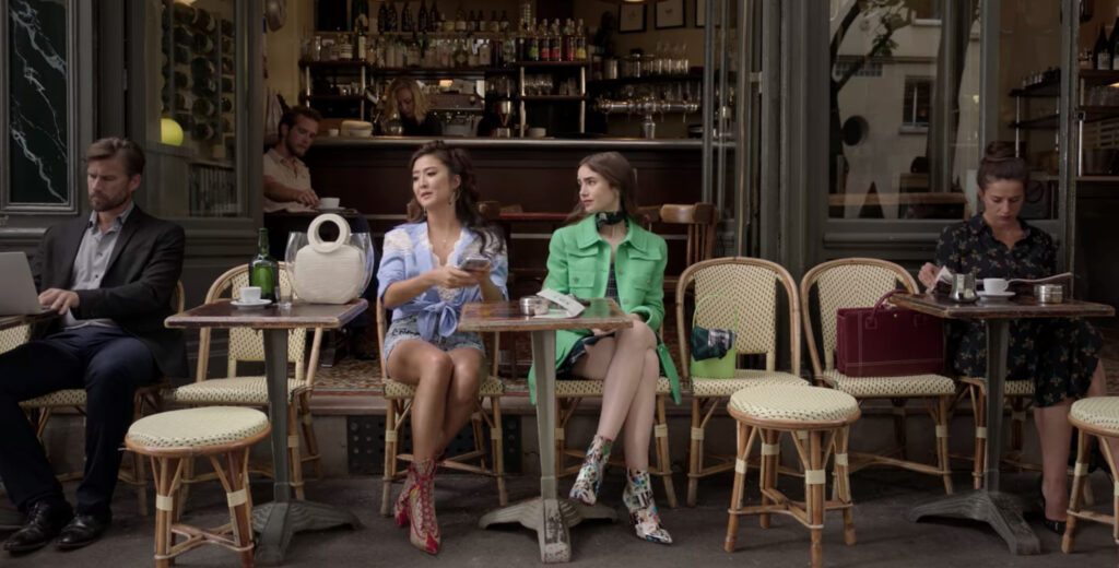 Mindy (left) and Emily (right) sit at a cafe. Mindy is wearing a blue shirt tied around the waist over a white top and shorts. Emily is wearing a green jacket.