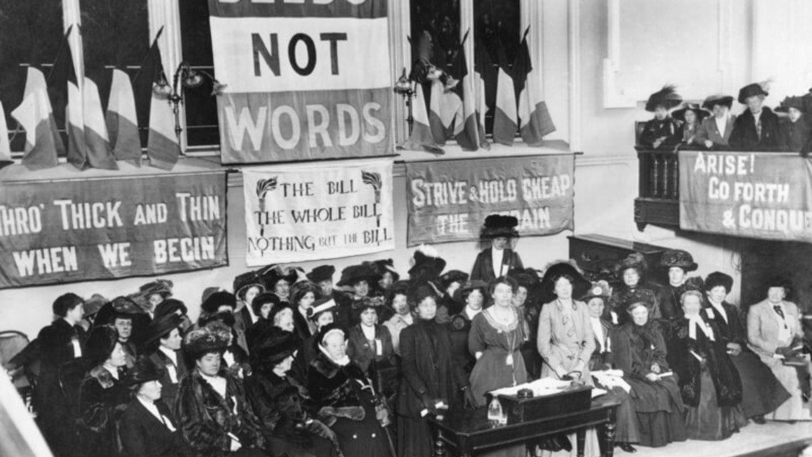 "A suffragette meeting in Caxton Hall, Manchester England. Banners showing the WSPU slogan ""Deeds Not Words"" hang above."