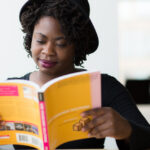 Woman in Black Long-sleeved Shirt Reading a Yellow Covered Book. via Pexels