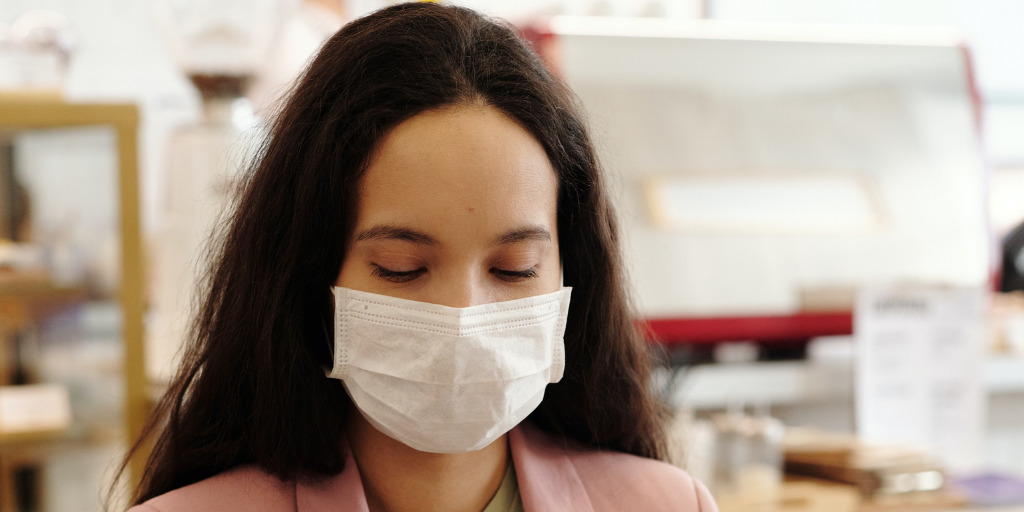A young woman wears a face mask while at office.