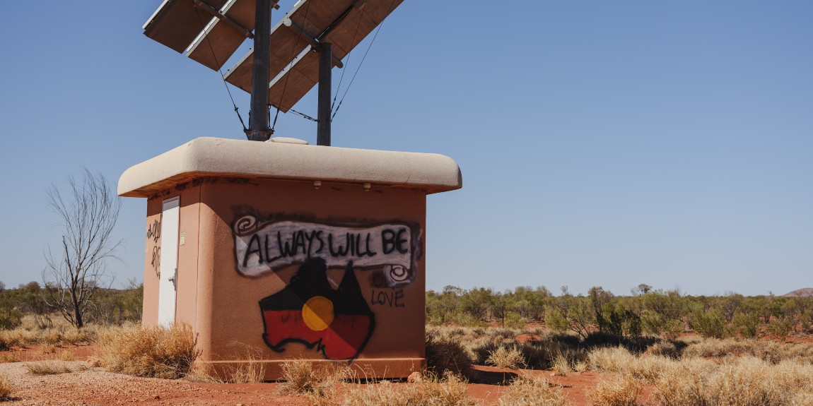 """Graffiti on a shed saying """"Always will be"""" with the map of Australia and the Australian Aboriginal flag."""